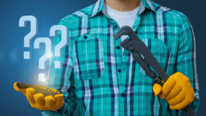 A man with a blue striped polo and yellow gloves is holding a wrench